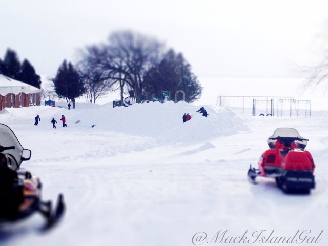 The kids of Mackinac Island Public School, enjoying their large wall of snow/snow hill