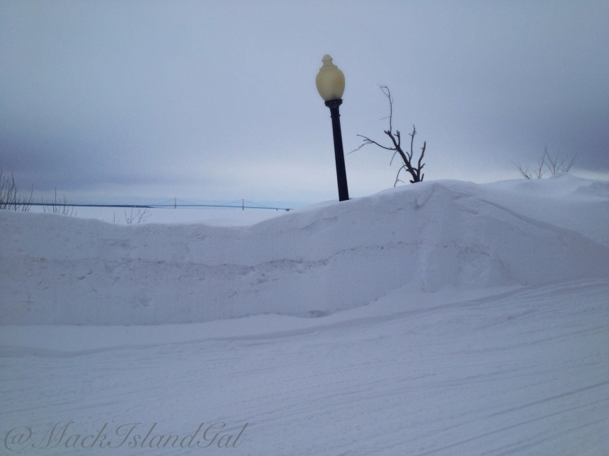"""This wall of snow taller than my 5'2"""" self nearly blocks out the view of the Mackinac Bridge"""